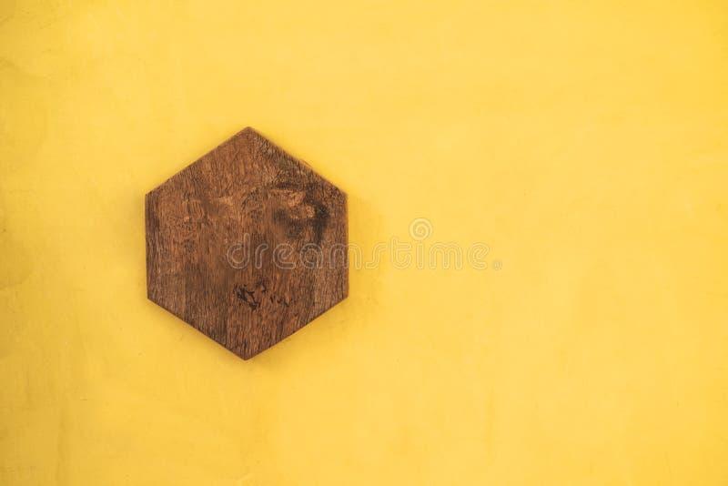 Placa de madera del hexágono en fondo amarillo de la pared imágenes de archivo libres de regalías