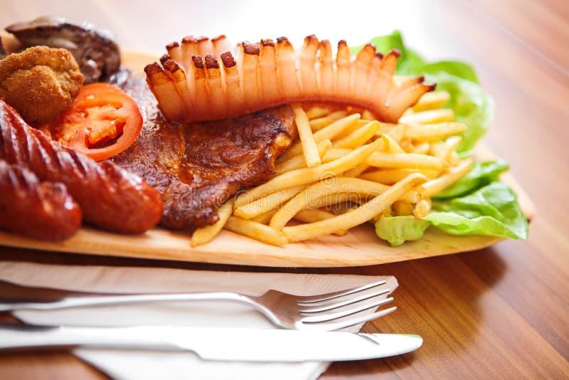 Placa de madera por completo de la comida sabrosa foto de archivo