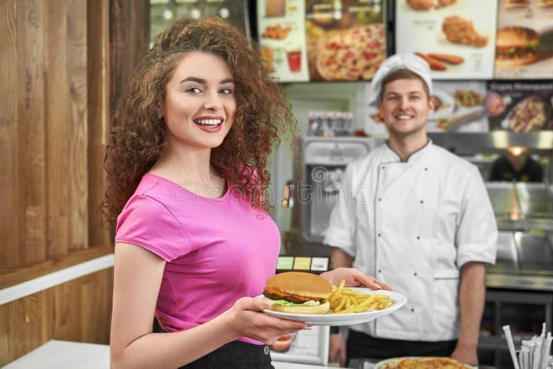 Placa de mantimento da mulher com fast food e sorriso no café fotos de stock royalty free