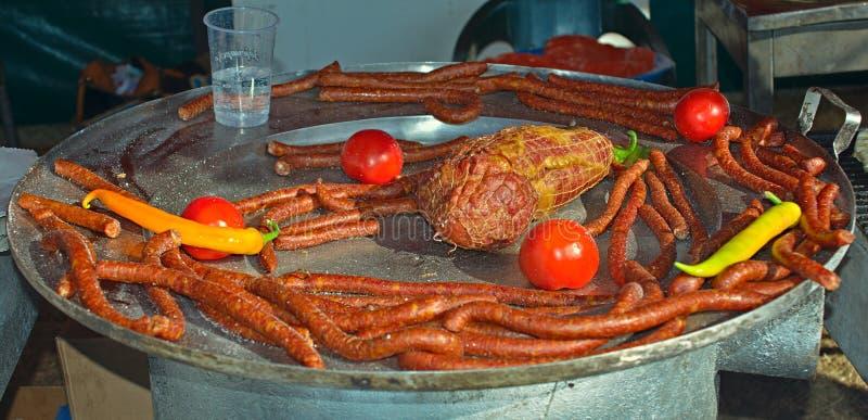 Placa de metal con las salchichas asadas a la parrilla, el jamón y algunas verduras imagen de archivo