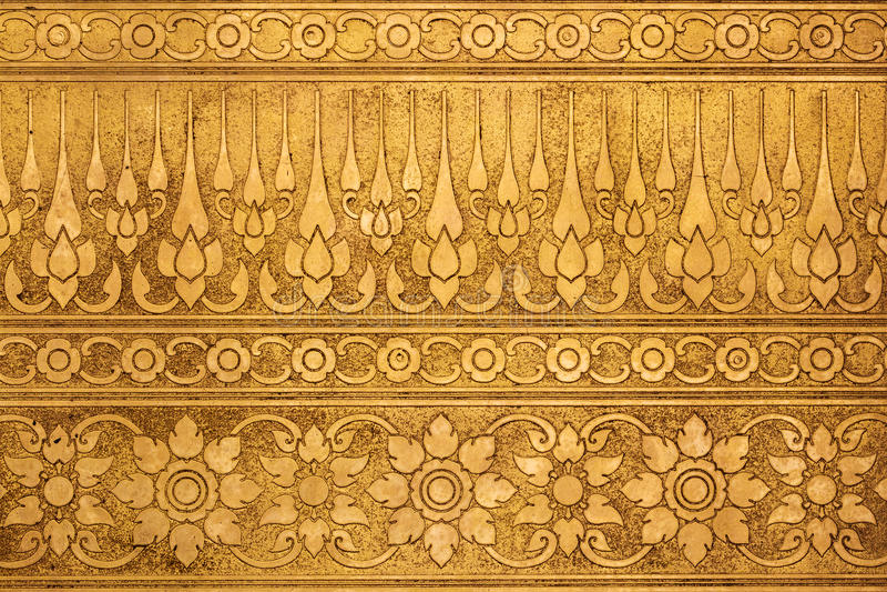 Placa de metal del oro viejo con la talla tradicional tailandesa imagenes de archivo