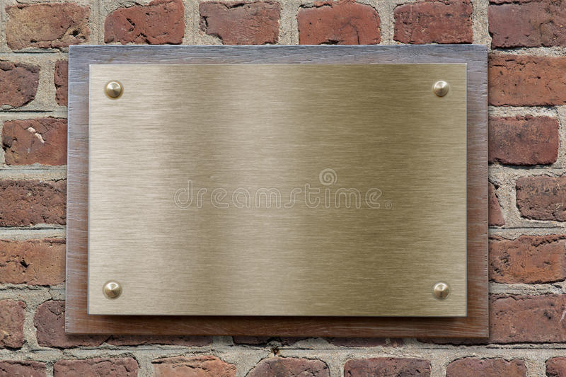 Placa de metal do bronze ou do bronze no brickwall foto de stock