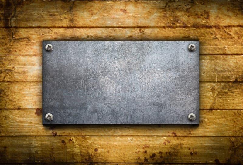 Placa de metal industrial en un fondo de madera foto de archivo