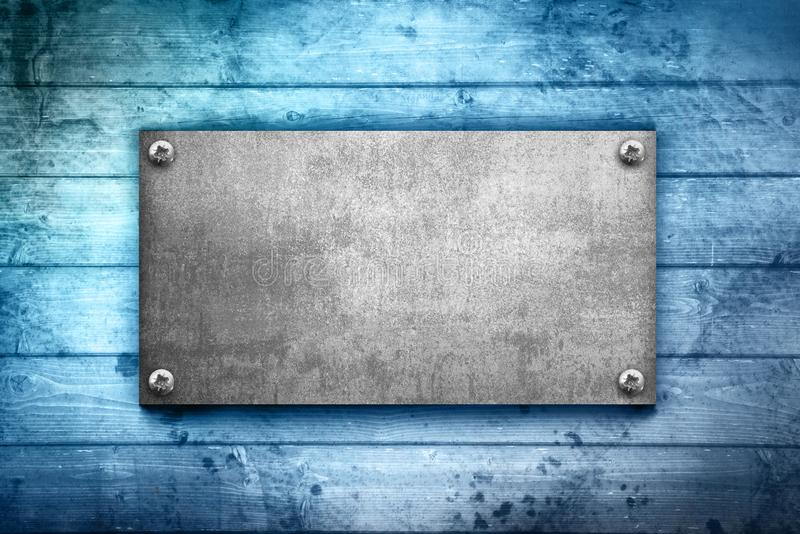 Placa de metal industrial en un fondo de madera fotografía de archivo
