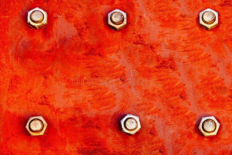 A placa de metal vermelha pintada com cores vermelhas e alaranjadas fortes e fixada com seis grandes parafusos de aço parafusa co imagens de stock royalty free