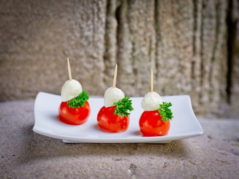 Placa de muchos mini tomate del tamaño de la mordedura y queso del mozarella sandwic imágenes de archivo libres de regalías