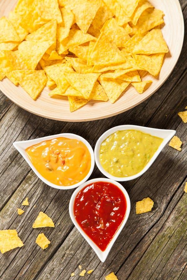Placa de nachos con diversas inmersiones imagen de archivo