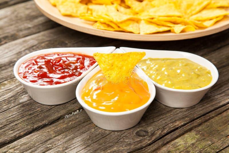 Placa de nachos con diversas inmersiones foto de archivo