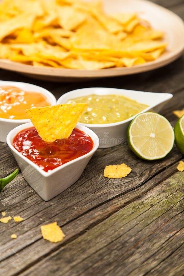 Placa de nachos con diversas inmersiones imágenes de archivo libres de regalías