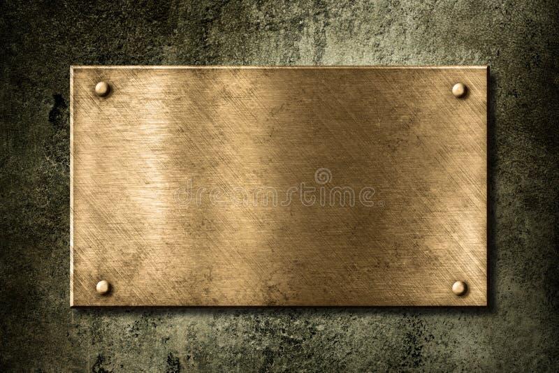 Placa de oro o de bronce vieja en la pared fotografía de archivo