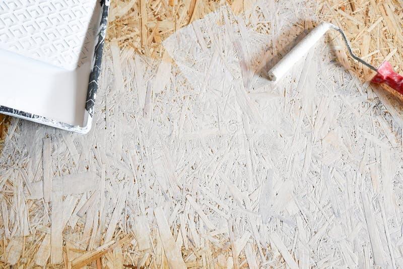 Placa de Osb pintada com pintura branca com um rolo fotos de stock