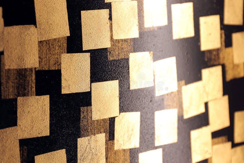 Placa de ouro no preto da parede, folha de ouro, folha quadrada dourada no fundo preto, parede preta da telha com textura do sumá imagens de stock