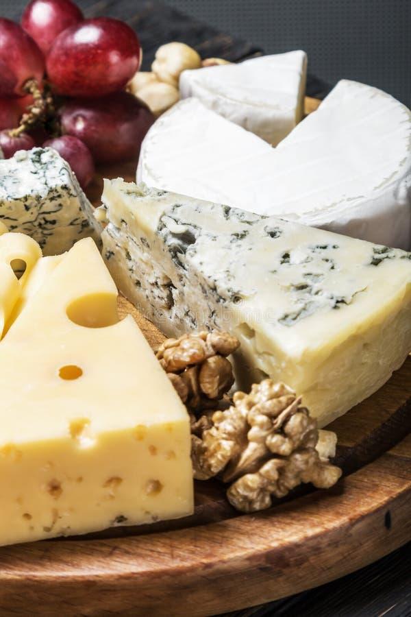 Placa de queijo com frutos e porcas em um de madeira fotos de stock