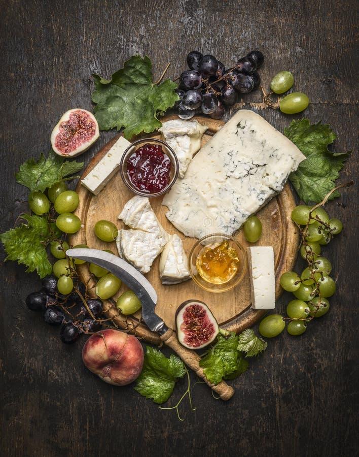 Placa de queijo com gorgonzola e queijo do camembert com a faca para as uvas do queijo, o mel e o doce brancos e escuros em um co fotos de stock