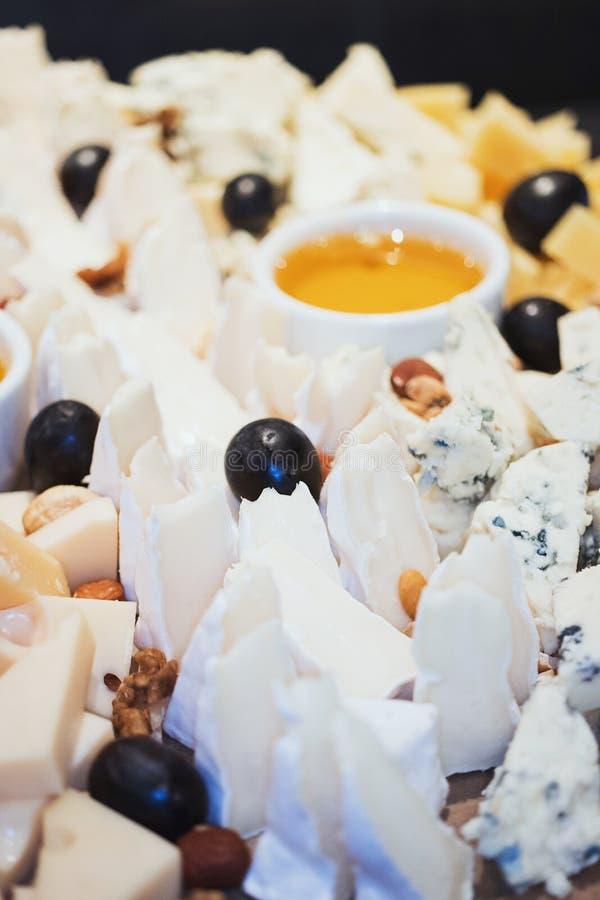 Placa de queijo A variedade do queijo com nozes e o mel do dipper do mel no serviço de madeira branco embarcam sobre o textur con fotografia de stock