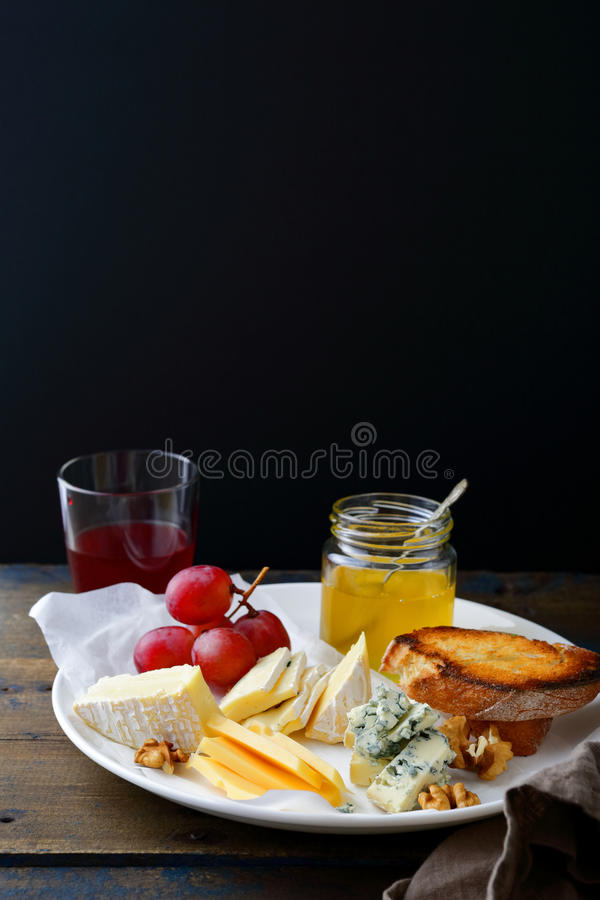 Placa de queso con las uvas, la miel, el pan, las nueces y el vino en fondo negro foto de archivo libre de regalías