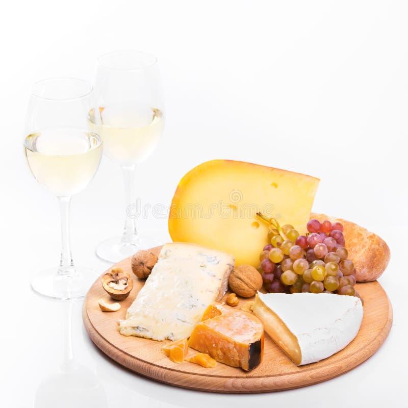 Placa de queso con las uvas y el vino blanco fotos de archivo libres de regalías