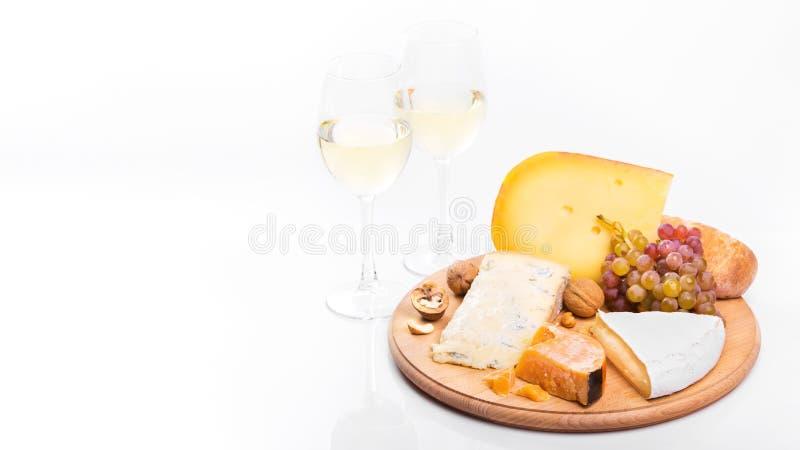 Placa de queso con las uvas y el vino blanco imagenes de archivo
