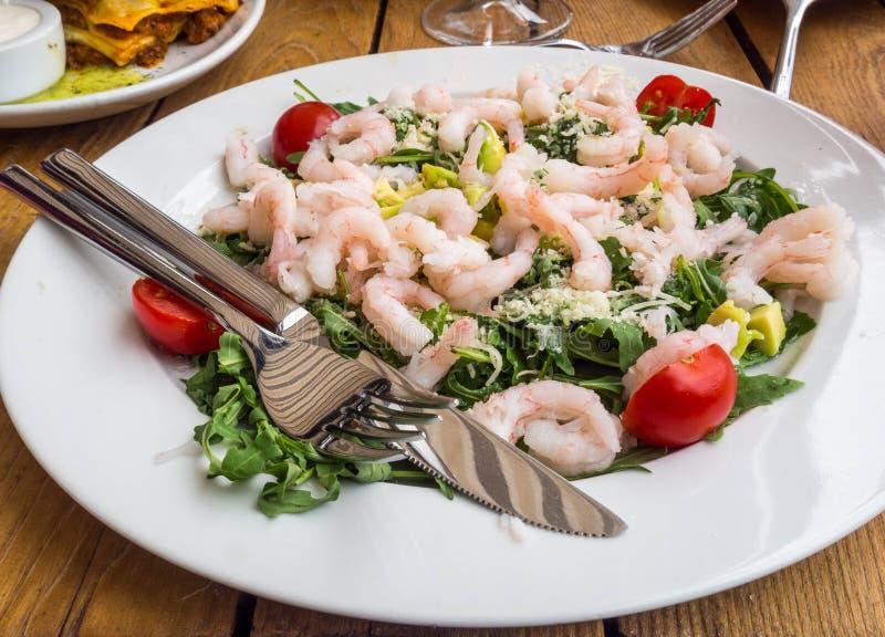 Placa de salada fresca com camarão, abacate, tomate e rúcula misturada dos verdes, mesclun, mache no fim de madeira do fundo acim foto de stock