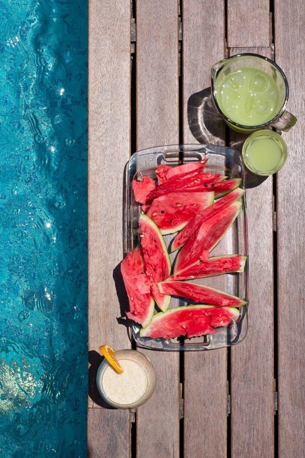 Placa de sandía y tintes de verano cerca de la piscina Dieta de verano exótica El estilo de vida de las playas tropicales fotos de archivo
