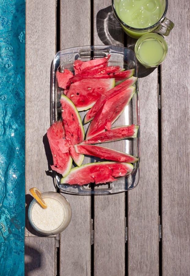 Placa de sandía y tintes de verano cerca de la piscina Dieta de verano exótica El estilo de vida de las playas tropicales imagen de archivo