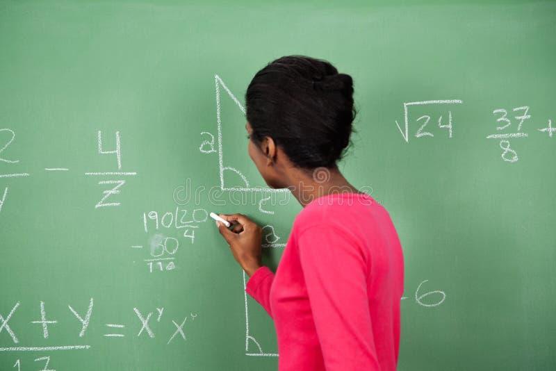 Placa de Solving Mathematics On do professor fêmea imagens de stock royalty free