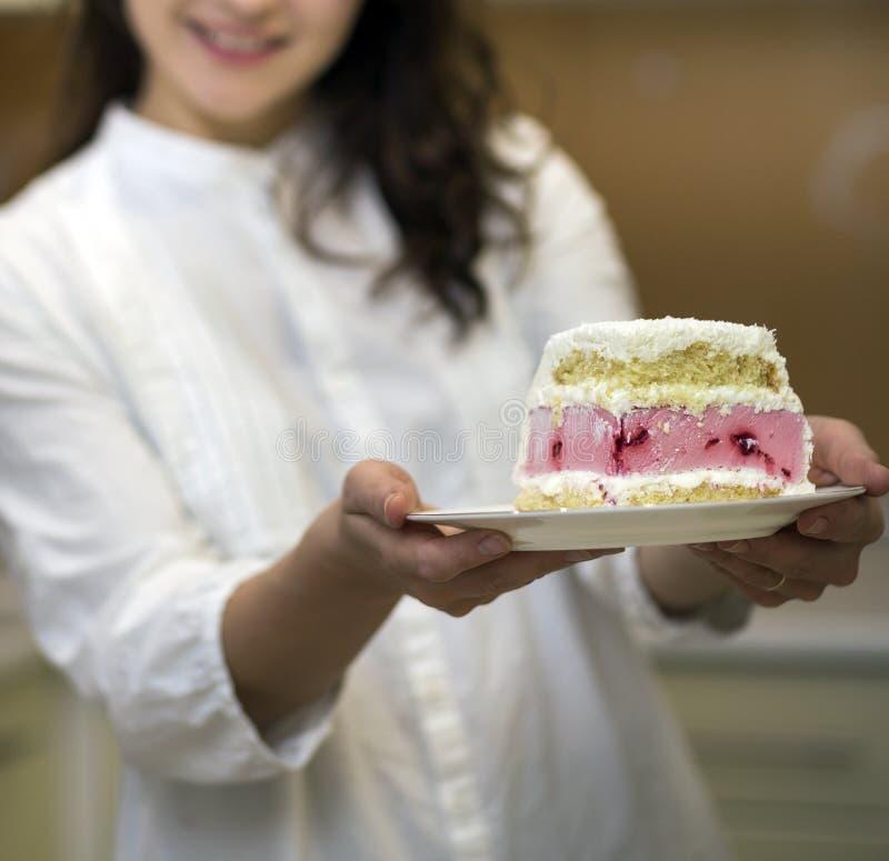 Placa de sorriso atrativa nova da terra arrendada da mulher com parte caseiro saboroso deliciosa fresca do bolo cremoso branco e  imagem de stock