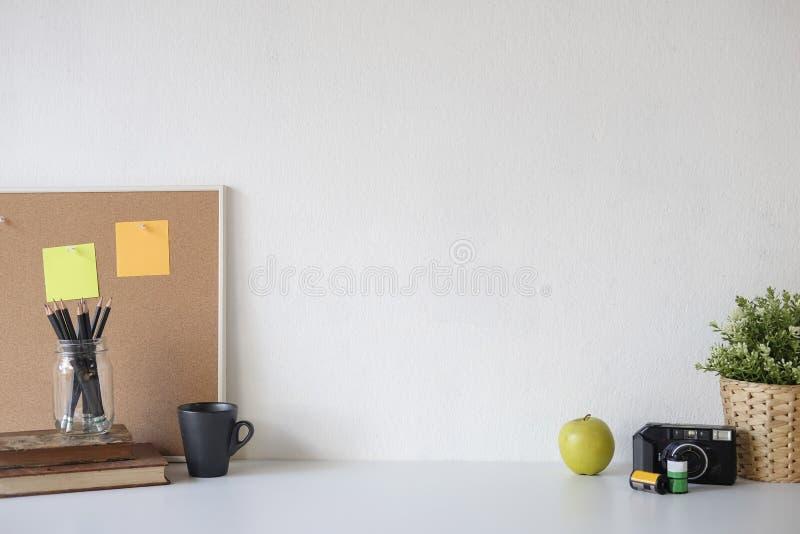 Placa de tabela e caneca à moda do post-it, do livro, do lápis, da câmera e de café na tabela com parede fotografia de stock
