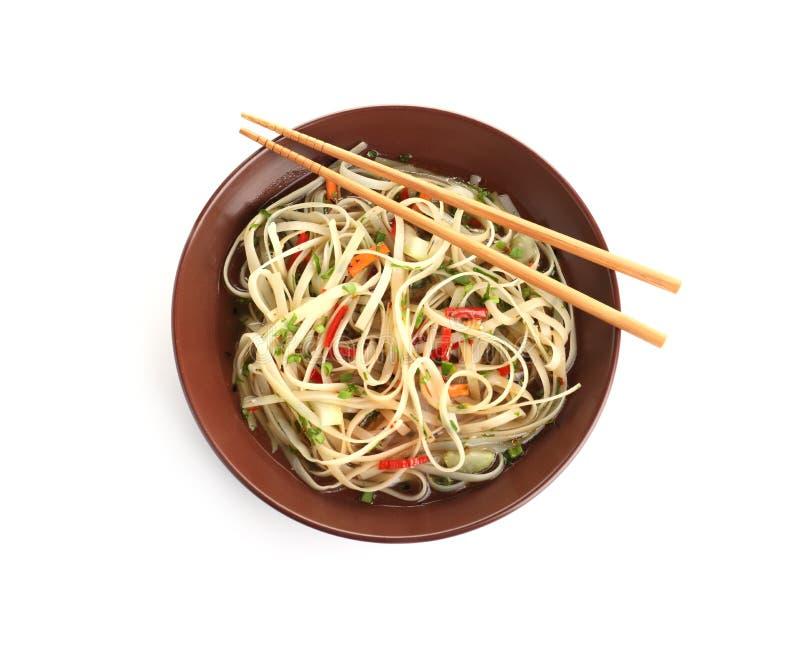 Placa de tallarines deliciosos con el caldo, las verduras y los palillos aislados en blanco foto de archivo