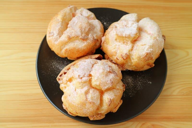 Placa de tres soplos poner crema o Choux franceses pasteles de una nata del la servidos en la tabla de madera fotos de archivo libres de regalías