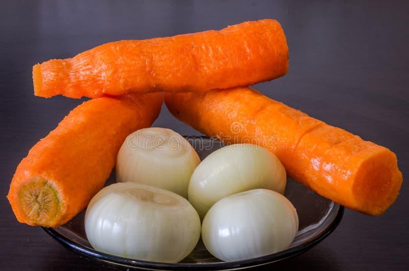 A placa de vidro na tabela preta com as cebolas vermelhas cruas refinadas e as cenouras cozinham o cozimento foto de stock