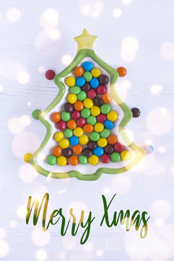 Placa del árbol de navidad con los caramelos coloridos en un fondo blanco Feliz tarjeta de Navidad con el bokeh fotos de archivo libres de regalías