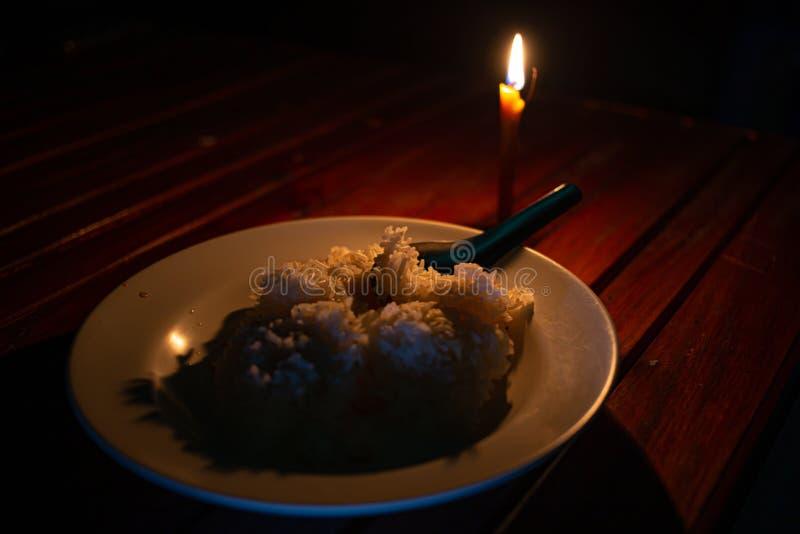 Placa del arroz y luz de la vela foto de archivo