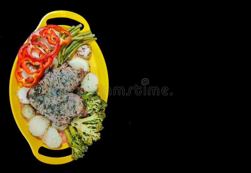Placa del filete y de las verduras en una placa amarilla en un fondo negro con el espacio para el texto foto de archivo libre de regalías