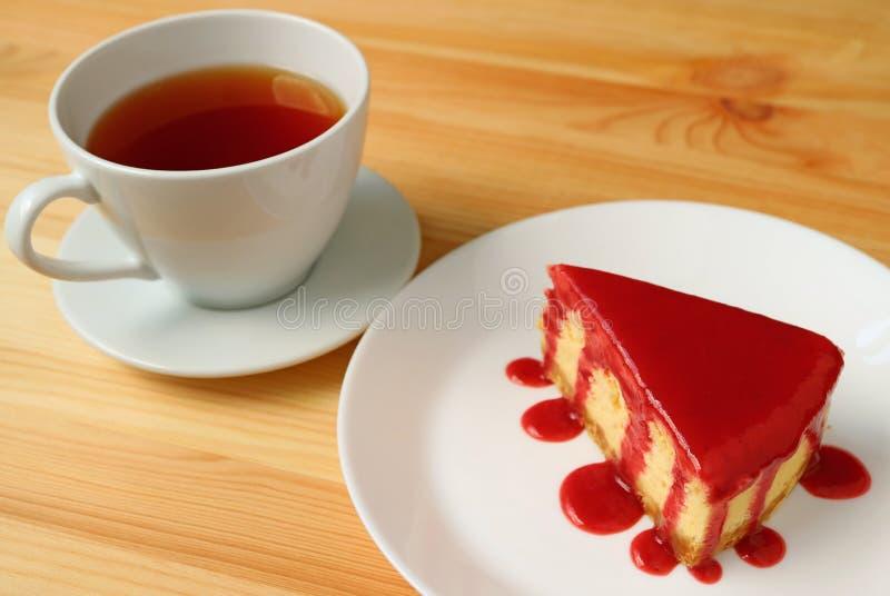 Placa del pastel de queso cocido con la salsa de la frambuesa con una taza de té caliente servida en la tabla de madera fotografía de archivo