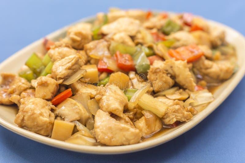 Placa del pollo del ajedrez, una comida china en fondo azul fotos de archivo