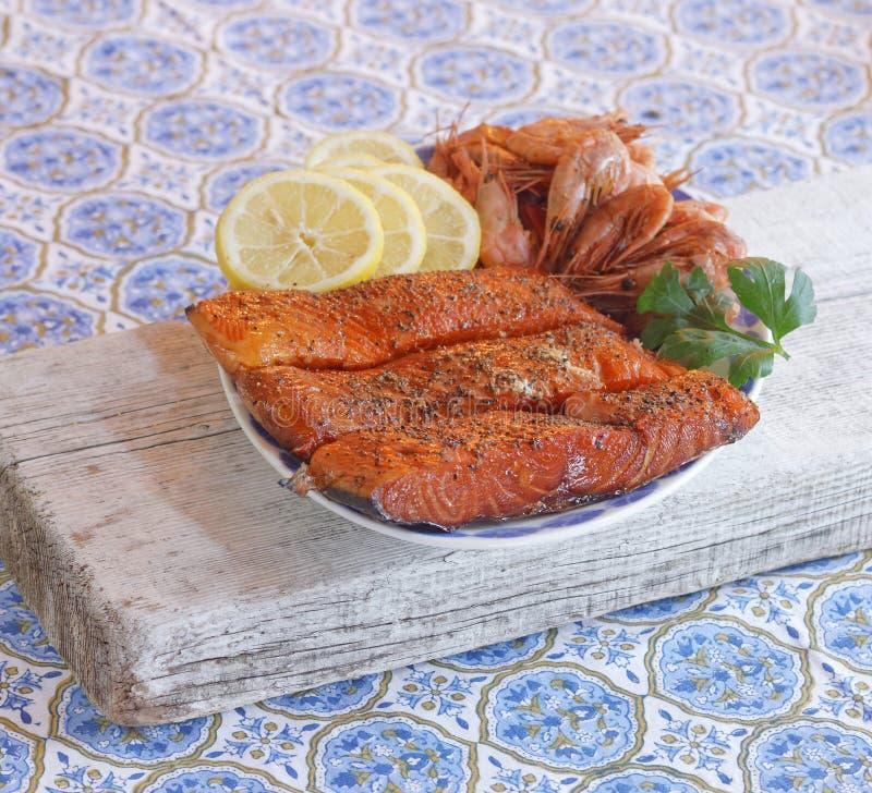 Placa del salmón ahumado, camarones, limón y parsely imagenes de archivo