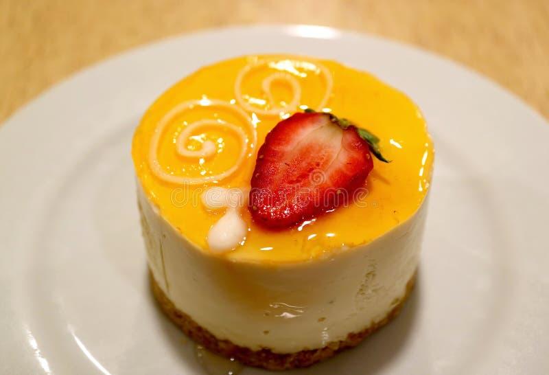 A placa do bolo de queijo do fruto de paixão cobriu com morango fresca fotos de stock royalty free