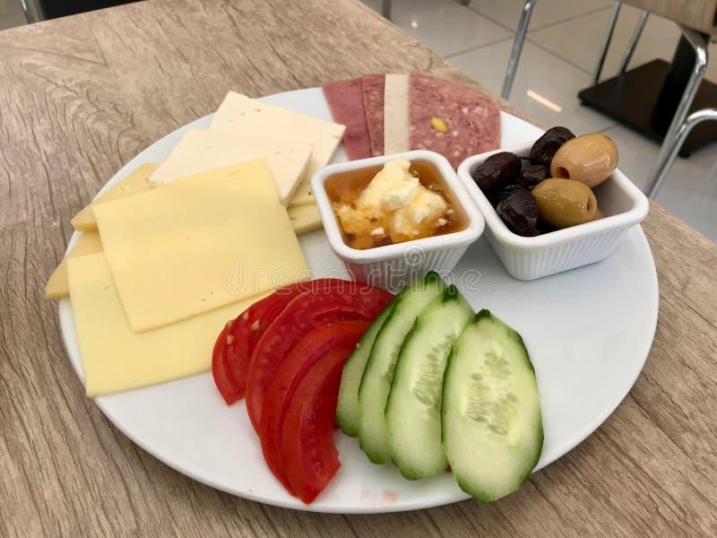 Placa do café da manhã do turco com mel, manteiga Kaymak de creme, queijo, fatias do pepino, azeitonas, presunto e tomates fotografia de stock royalty free