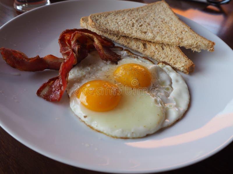 Placa do caf? da manh? com ovos fritos, bacon e brindes foto de stock