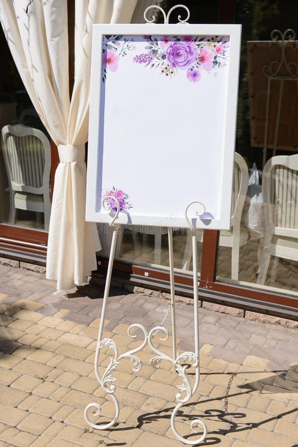 Placa do casamento no suporte forjado branco com uma lista do convidado foto de stock royalty free