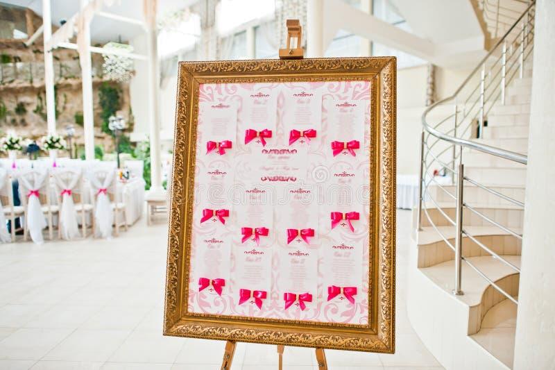 Placa do convidado do casamento com as fitas cor-de-rosa no salão do casamento fotografia de stock royalty free