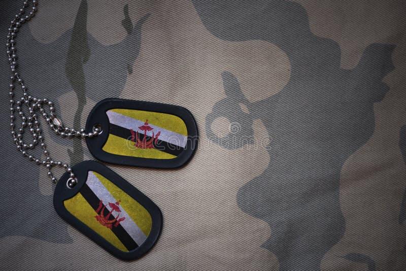 Placa do exército, etiqueta de cão com a bandeira de brunei no fundo caqui da textura imagens de stock