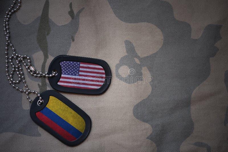 placa do exército, etiqueta de cão com a bandeira de Estados Unidos da América e Colômbia no fundo caqui da textura fotos de stock