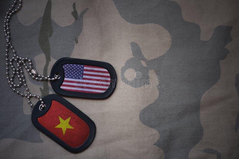 placa do exército, etiqueta de cão com a bandeira de Estados Unidos da América e Vietnam no fundo caqui da textura fotos de stock royalty free
