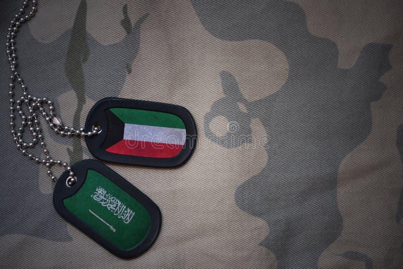 placa do exército, etiqueta de cão com a bandeira de kuwait e Arábia Saudita no fundo caqui da textura fotos de stock royalty free