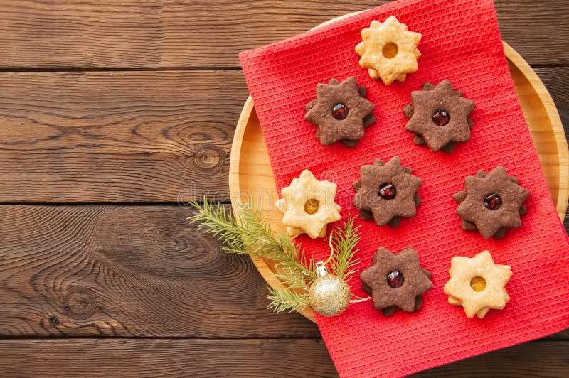 A placa do linzer do chocolate e da baunilha star cookies com raspberr fotos de stock