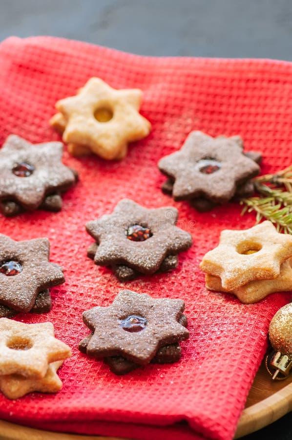 A placa do linzer do chocolate e da baunilha star cookies com raspberr foto de stock