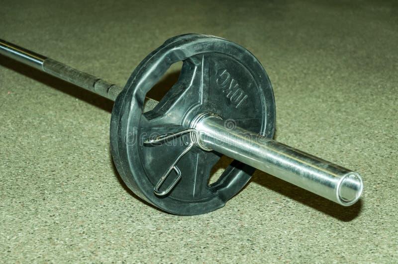 Placa do peso do Barbell no assoalho do gym pronto para uso para o exercício fotos de stock