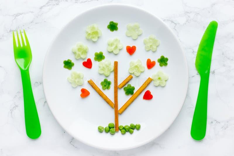 A placa do petisco dos vegetais deu forma à arte verde do alimento do tema da árvore, da primavera e do amor foto de stock